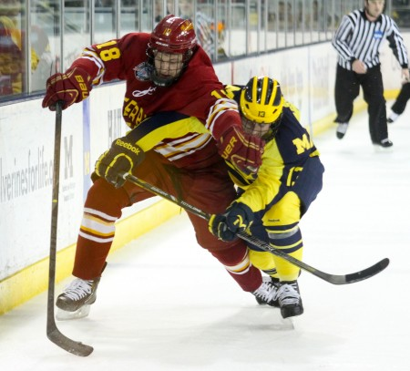 Keeping at Bay: Ferris junior left wing Andy Huff attempts to hold a Michigan attacker back. The Bulldogs would tie and lose the shootout against the Wolverines for the final regular season game. Photo by Brock Copus | Multimedia Editor